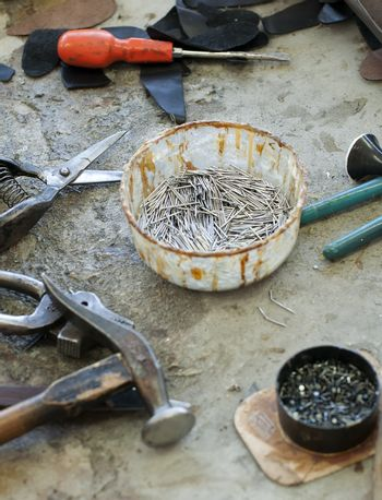 Tools for footwear and a bowl of nails