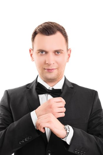 Close up portrait of a confident, stunning, trendy, attractive, dreamy, perfect man in black suit with bow tie, adjusting the cufflinks on his white shirt, looking at the camera, isolated on a white background.