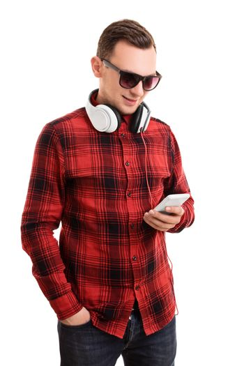 Modern and casual in style. Portrait of a confident smiling man or student in plaid shirt, sunglasses and headphones, looking at his mobile phone and texting, isolated on a white background.