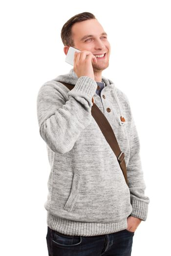Portrait of a confident smiling man or student in casual clothes and a shoulder bag talking on mobile phone, isolated on a white background.