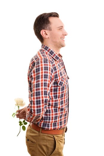 Valentine's Day concept. Portrait of a romantic stylish handsome young man hiding a white rose flower behind his back, standing and smiling, isolated on white background.