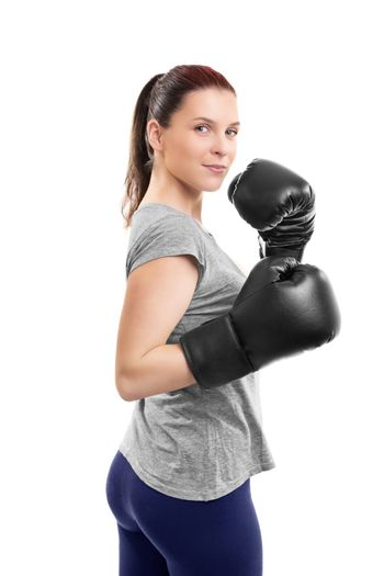 Portrait of a beautiful young woman with boxing gloves in a stance with raised arms, isolated on white background.