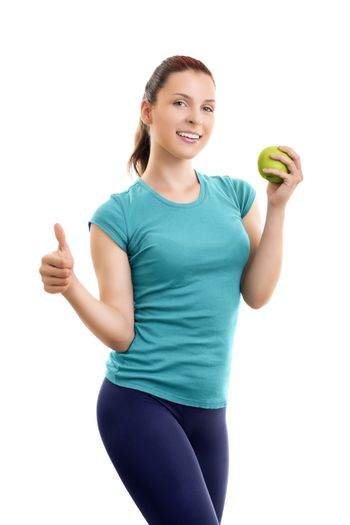 Healthy, lifestyle, diet, weight loss concept. Portrait of a confident, sporty, smiling beautiful young woman in sports clothes, holding a green apple and giving thumb up, isolated on white background.