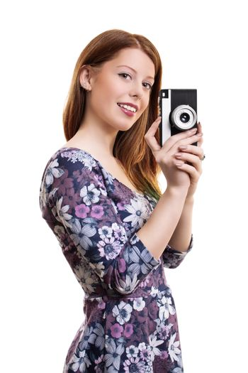 Side portrait of a fashinable, beautiful smiling young girl taking a photo with an old film vintage camera, isolated on white background.