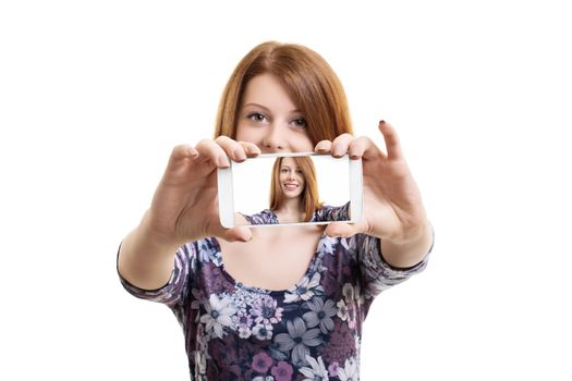 Beautiful smiling fashionable young woman taking a selfie with a smartphone, isolated on a white background.