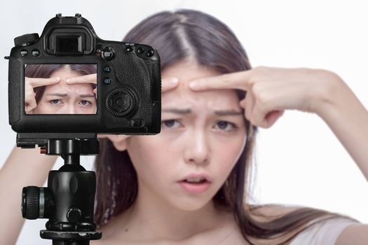 Asian American woman squeezing a spot on her forehead, social media concept