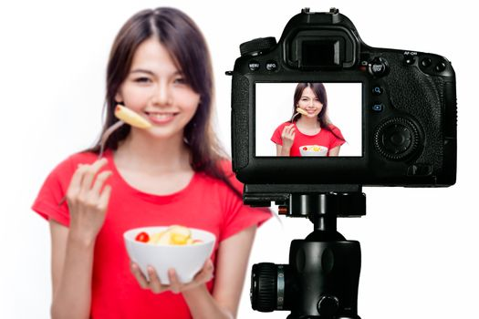 Asian food vlogger with fruit salad behind camera, social media production concept