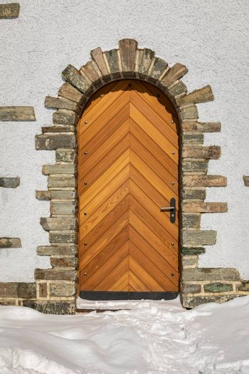 Wooden door on white building decorated by birck with snow outside in winter.