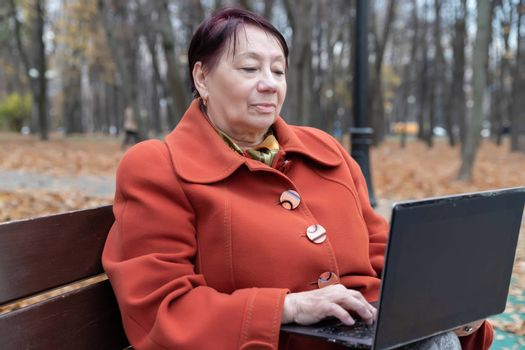 An elderly woman in a bright terracotta coat sits on a bench in an autumn Park with a laptop and selects goods online