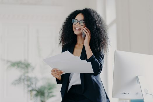 Pleased successful businesswoman with Afro hairstyle wears spectacles to provide eyes protection, holds documents, makes telephone call to business partner, stands in cabinet near workplace.