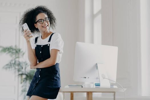 Happy curly haired girl uses mobile phone for communication and keeping in touch, wears spectacles and casual clothes, leans at desktop, poses in spacious cabinet. Glad student uses technology