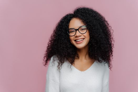 Headshot of pleased lovely woman with curly hairstyle, smiles gently at camera, wears optical glasses and white casual sweater, poses against purple background. Positive emotions and feelings concept