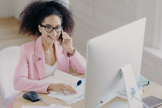 Positive dark skinned woman with curly combed hair, keybaords on computer, involved in working process, wears spectacles and elegant clothing, has telephone conversation, poses at workplace.