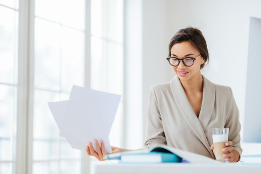 Horizontal view of confident brunette female worker in formal wear and optical spectacles looks through documentation, drink fresh beverage, focused down, poses indoor, has pleased expression