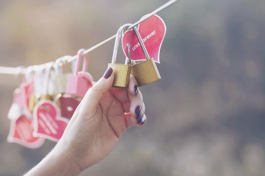 Lady hand holding padlock key with heart symbol of love on bridge - culture of love sign symbol concept