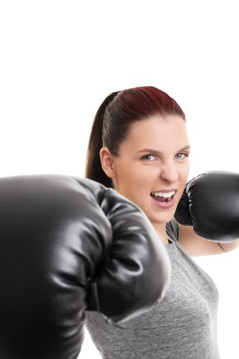 Close up shot of a young beautiful girl with boxing gloves punching the camera, isolated on white background.