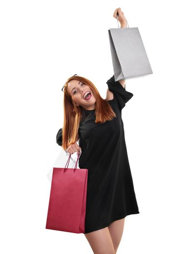 Sale, shopping concept.Portrait of an excited beautiful young woman with shopping bags in both hands, isolated on white background.