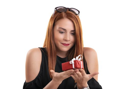 Portrait of a beautiful smiling girl holding a small wrapped gift box in both hands, isolated on white background. Christmas, New Year, Valentine's gift concept.