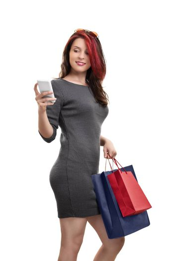 Portrait of a beautiful young woman in a dress holing shopping bags and looking at her phone, isolated on white background.