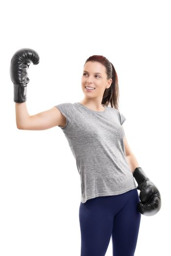 A portrait of a young beautiful girl with boxing gloves, raising one hand to celebrate her success, isolated on white background.