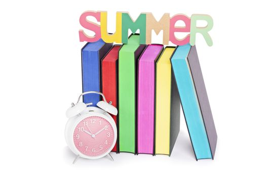 Summer, reading concept. Letters spelling SUMMER places over books with colorful sprayed edges and a clock, isolated on white background.