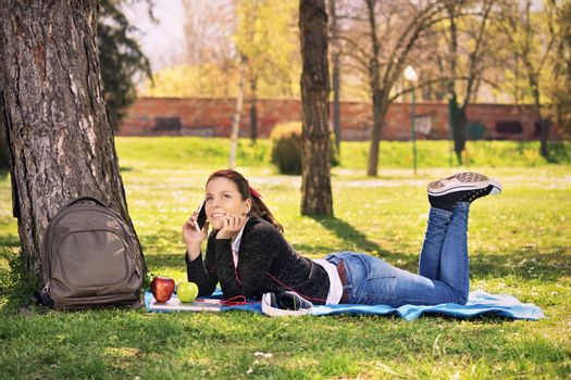 Beautiful young female student girl lying on the grass in a park, taking a break from studying and talking on the phone.