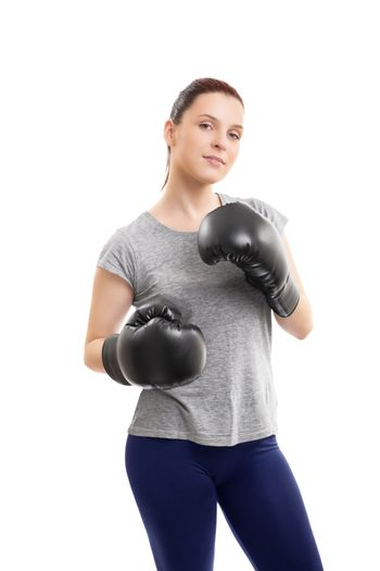 A portrait of a beautiful young woman with boxing gloves in a stance with raised arms, isolated on white background.