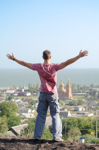 young athletic man spread his arms over the cliff