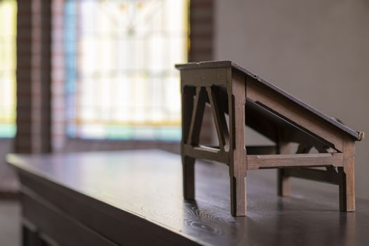 Wooden lectern in an old church with stained glass windows in the background
