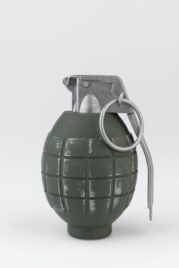 Green metal hand grenade against a white background