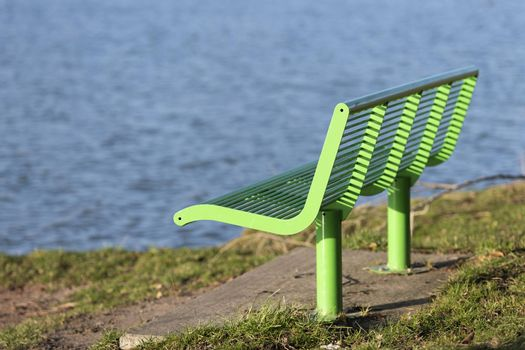 Green bench as street furniture in a grassy area on the waterfront