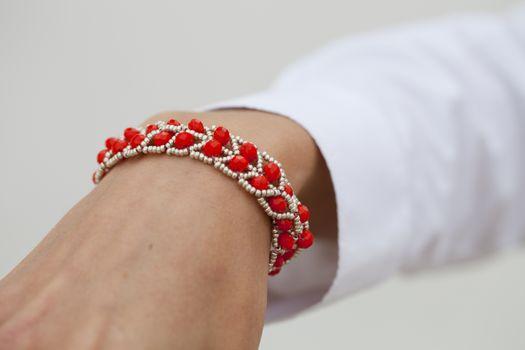 Stylish red bead bracelet on female hand