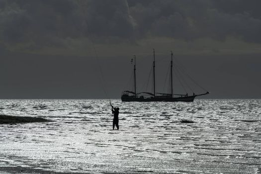 Contour of a three-masted sailboat and a kite surfer on the Wadden Sea near the island of Terschelling in the North of the Netherlands