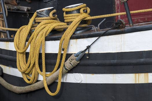 Yellow draped rope to a fishing boat in a harbour in the North of the Netherlands