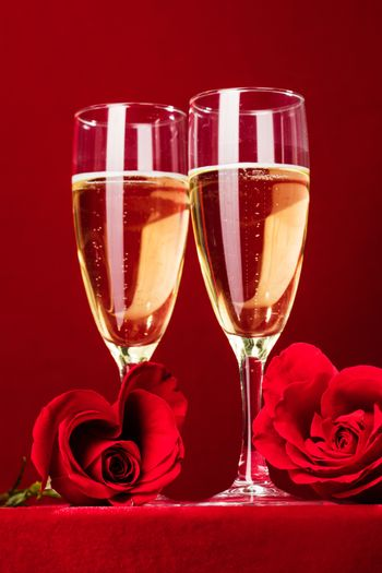 Champagne and red heart shaped roses on red background