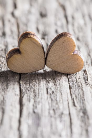 Two handmade wooden carved hearts on light wood background couple relationship Valentine day concept