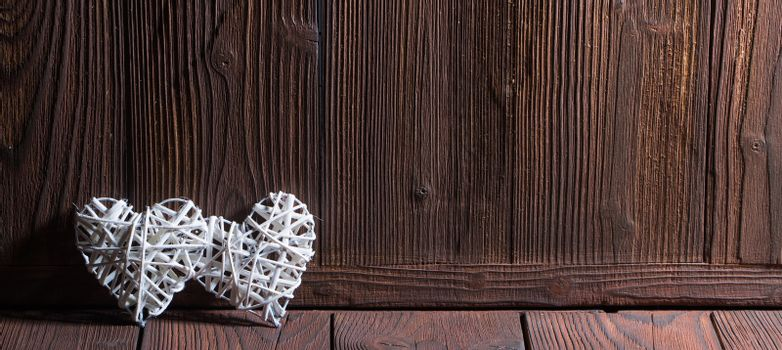Two wicker hearts on wooden background with copy space for text