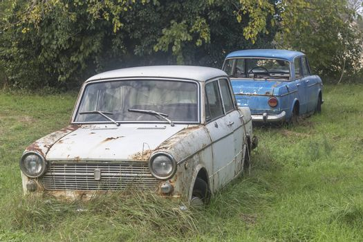 two old cars abandoned in the yard