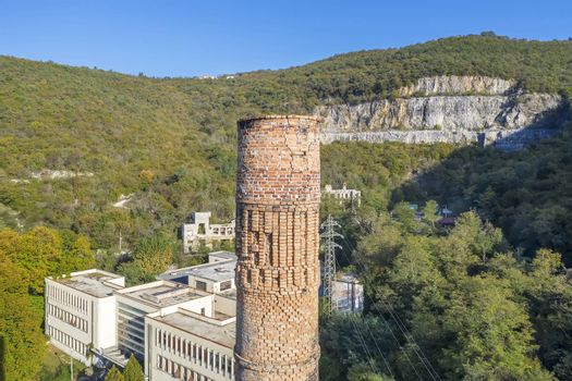 an aerial view of abandoned factory with chimney in forefront in Raša, Croatia