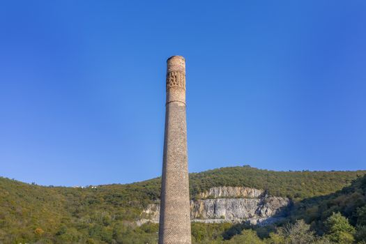tall old factory chimney made of brown bricks, an aerial view