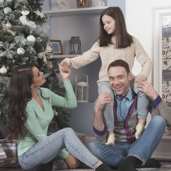 Family of parents and daughter hug in front of Christmas tree