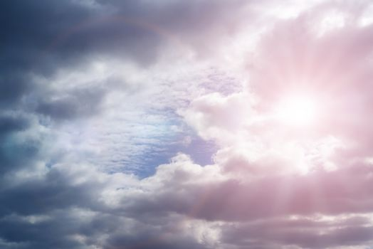 Sky with cumulus clouds and sunbeams on a summer day