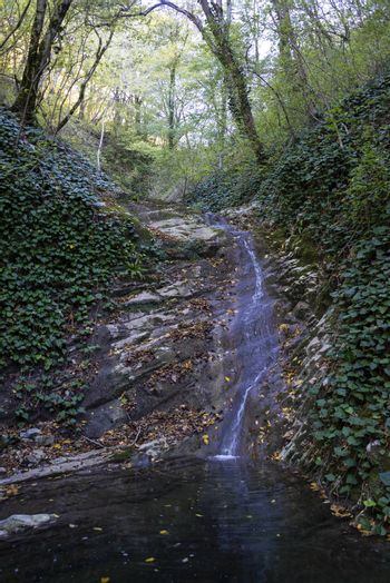 Waterfall in autumn on the tourist route Berendeevo Kingdom. It is a landmark of Lazarevsky district of Sochi, Russia. October 4, 2019.