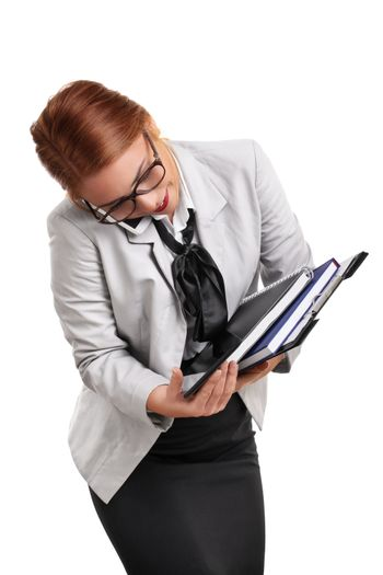 Portrait of a busy beautiful young businesswoman talking on the phone, trying to keep the notepads, clipboard and tablet from falling, isolated on white background. Multitasking concept.