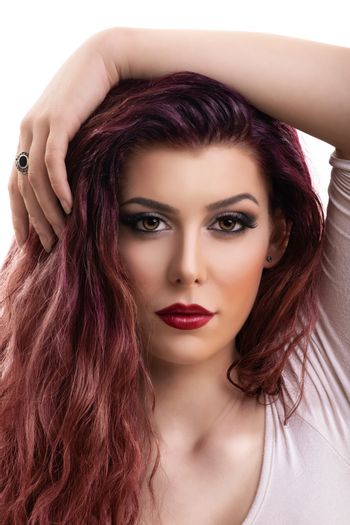 Close up profile shot of a beautiful redhead young woman with dark smokey eye makeup and red lipstick, isolated on white background. Female fashion. Beautiful young woman with perfect skin and long hair.