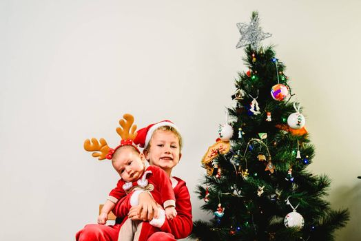 Toddler and newborn baby, siblings disguised as christmas, holiday concept