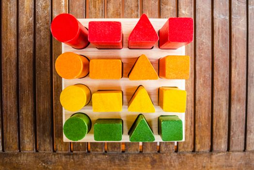 Set of blocks of wood of sequences of geometric shapes painted with natural dyes, seen from above, to help the motor development of children.