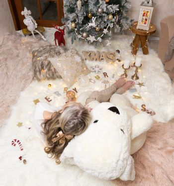 A female sits on rugs in front of the Christmas tree w
