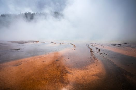 Smoke covered orange pond of Grand Prismatic Spring, famous geyser basin in Yellowstone National Park, Wyoming, USA.