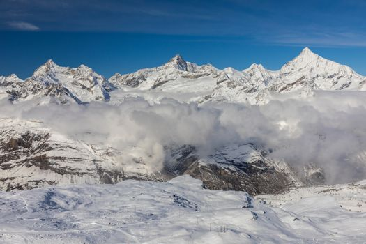 Aerial from top of Gornergrat mountain surrounded by snowcapped mountain range on sunny day, Zermatt, Switzerland.